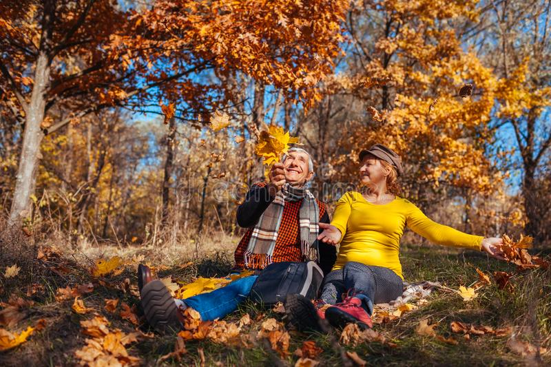 Autumn season fun. Senior couple throwing leaves sitting in park. Man and woman relaxing outdoors royalty free stock images