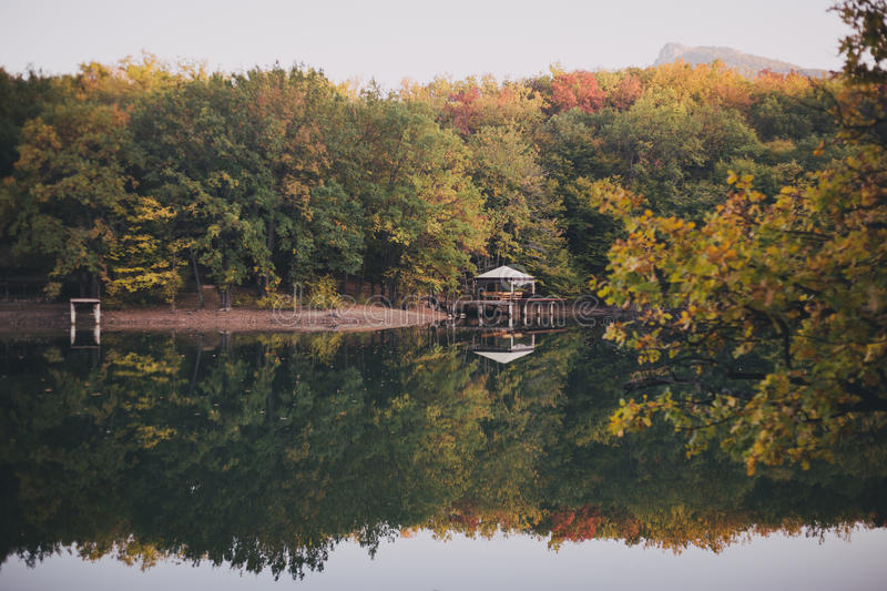 Autumn season landscape, forest and lake. With little house on it stock photo