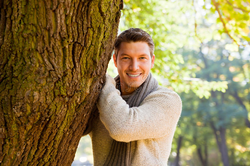 Autumn season man. Portrait of relaxing man on tree enjoying golden autumn fall season royalty free stock photography