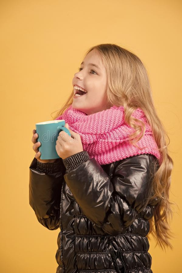 Autumn season relax concept. Child hold mug in black jacket and pink scarf. Tea or coffee break. Girl with blue cup smile on orange background. Hot drink in stock images