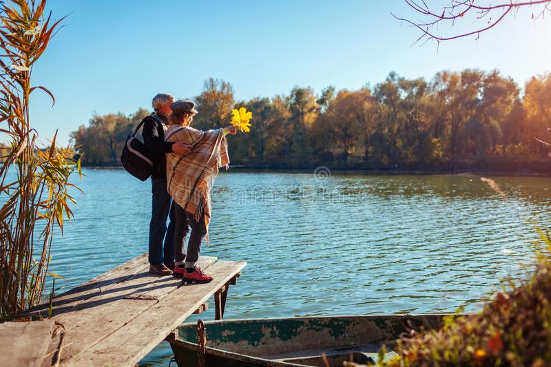 Senior family couple walking by autumn lake. Happy man and woman enjoying nature and hugging on pier stock images