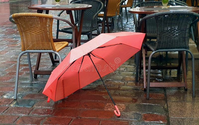Autumn season street cafe rainy day in the city lifestyle pink umbrella in the park medieval towers red roofs. Empty street cafe under rain ,Autumn season rainy stock photo