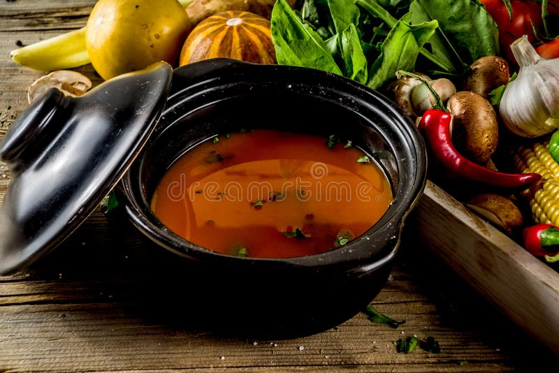 Autumn seasonal soup concept. Autumn seasonal cooking concept. Various autumn vegetables pumpkin,carrot,paprika,tomatoes,ginger with pot for cooking soup. wooden stock image
