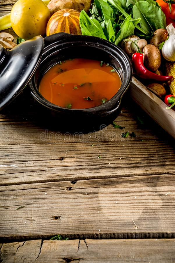 Autumn seasonal soup concept. Autumn seasonal cooking concept. Various autumn vegetables pumpkin,carrot,paprika,tomatoes,ginger with pot for cooking soup. wooden stock photo