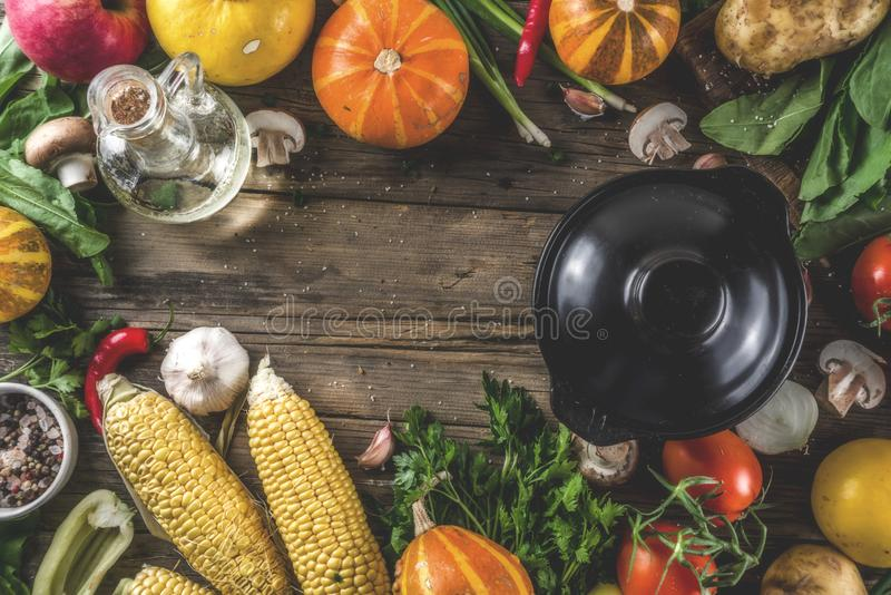 Autumn seasonal soup concept. Autumn seasonal cooking concept. Various autumn vegetables pumpkin,carrot,paprika,tomatoes,ginger with pot for cooking soup. wooden stock images