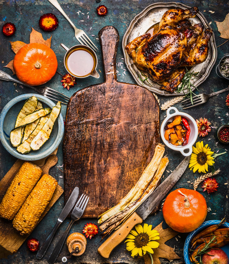 Autumn seasonal cooking and eating background with cutting board, roasted organic harvest vegetables , pumpkin, whole turkey or ch royalty free stock images