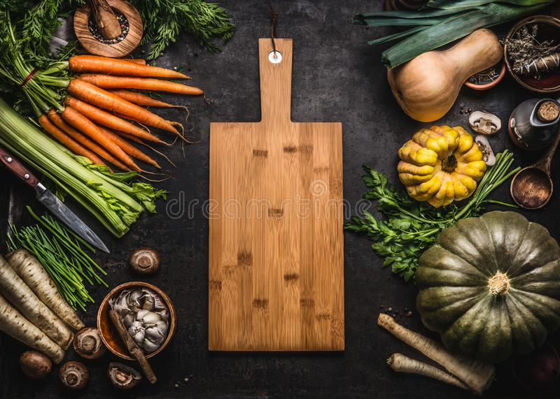 Autumn seasonal food background with colorful various pumpkins and organic farm vegetables around wooden cutting board, top view. stock images