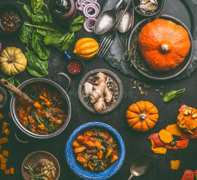 Autumn seasonal food and cooking with pumpkin. Dark rustic kitchen table with tools, bowls, spoons, whole and cut pumpkin and me. Als, top view. Vegetarian food royalty free stock photography