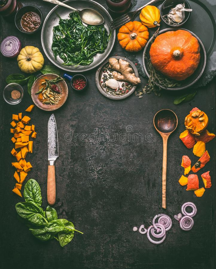 Autumn seasonal food, eating and cooking background with pumpkin. Dark rustic kitchen table with tools. Bowls, spoons, knife, whole pumpkin and vegetables, top stock photography
