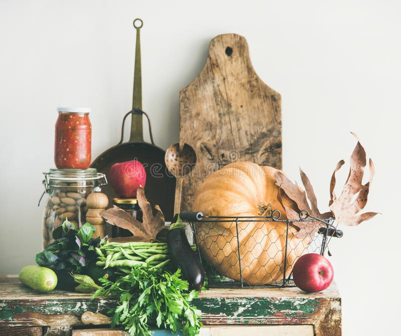 Autumn seasonal food ingredients and kitchen utensils over wooden cupboard royalty free stock image