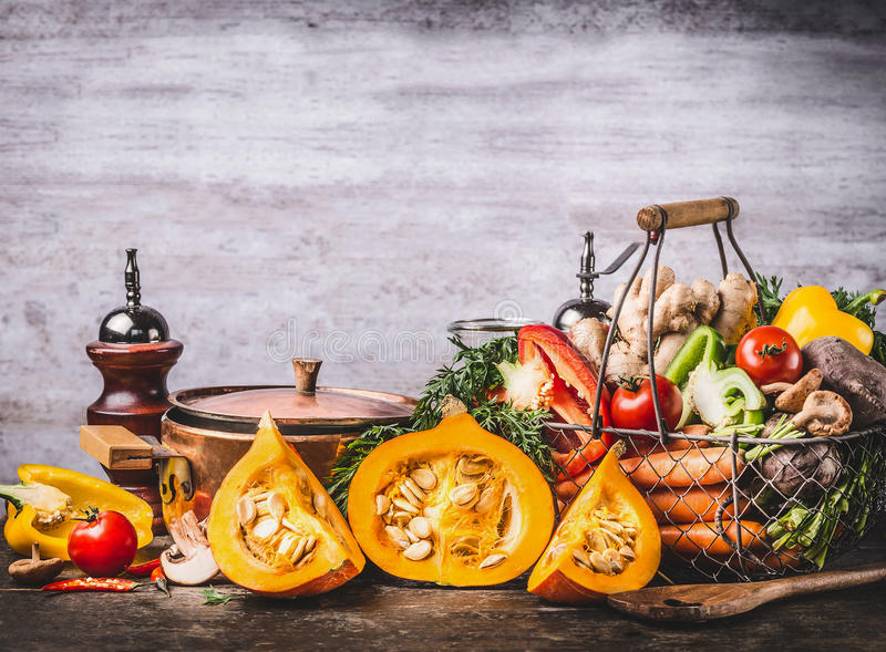 Autumn seasonal food still life with pumpkin, mushrooms, various organic harvest vegetables and cooking pot on rustic kitchen tabl. E background, front view royalty free stock photography