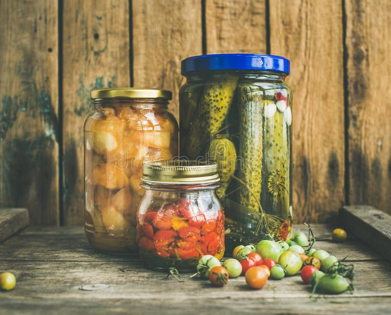 Autumn seasonal pickled vegetables and fruit in glass jars stock photo