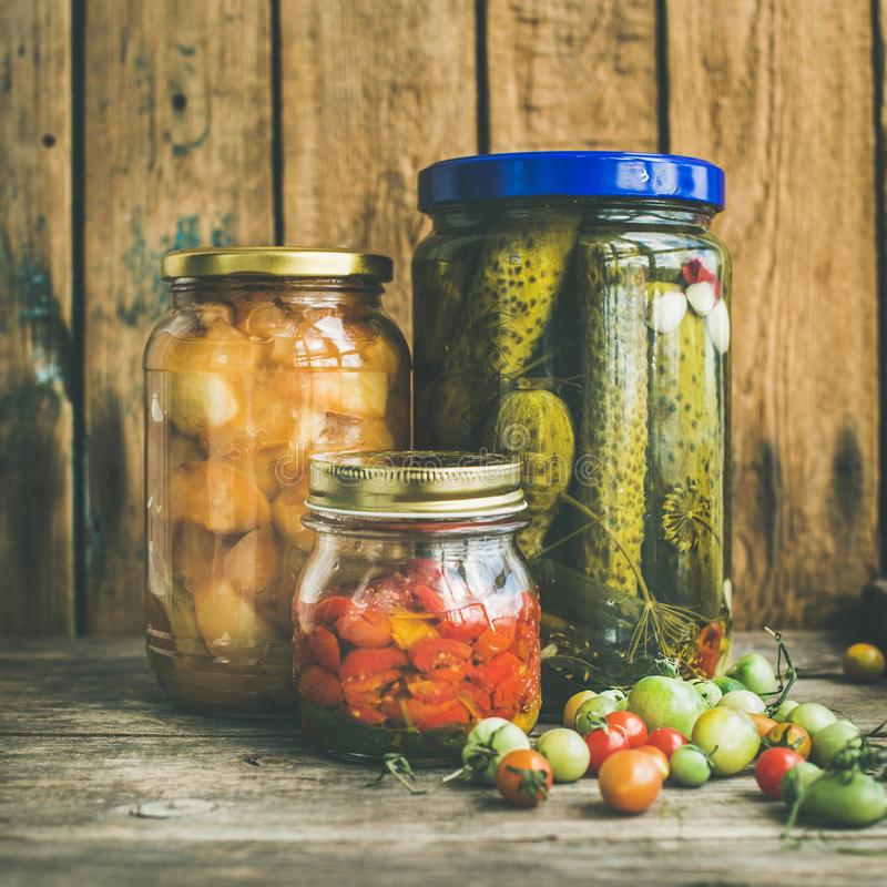Autumn seasonal pickled vegetables and fruit in jars, square crop stock image