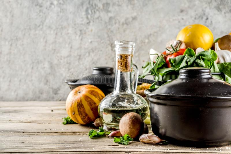 Autumn seasonal soup concept. Autumn seasonal cooking concept. Various autumn vegetables pumpkin,carrot,paprika,tomatoes,ginger with pot for cooking soup. wooden royalty free stock image