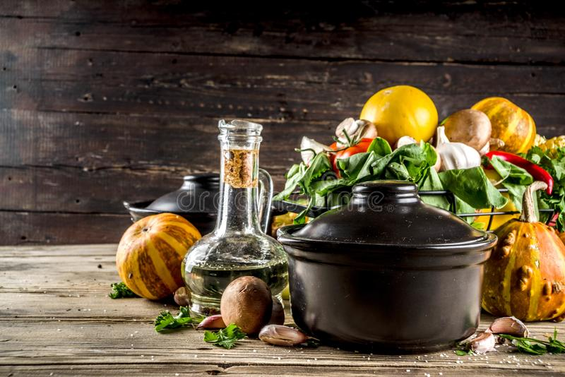 Autumn seasonal soup concept. Autumn seasonal cooking concept. Various autumn vegetables pumpkin,carrot,paprika,tomatoes,ginger with pot for cooking soup. wooden royalty free stock photography
