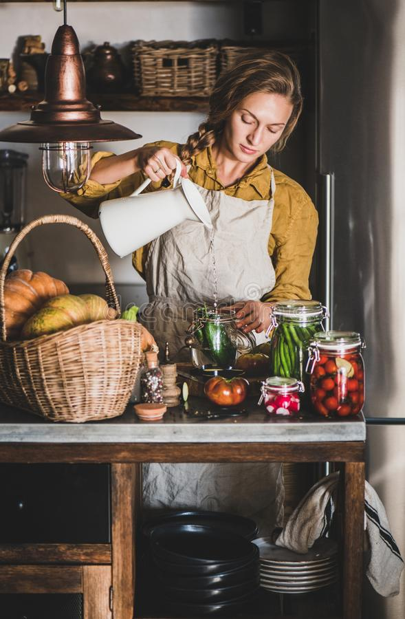 Young blond woman in apron making homemade vegetable preserves royalty free stock image