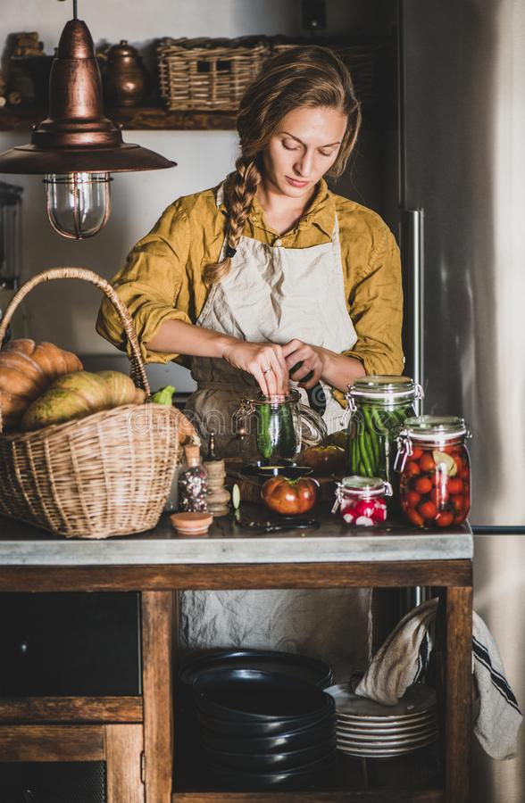 Young blond woman in apron cooking vegetables preserves in kitchen royalty free stock image