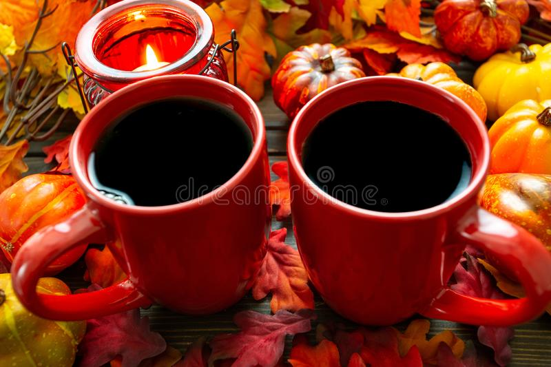Autumn setting with small pumpkins and a red candle holder emitting light on two cups of morning coffee royalty free stock photo