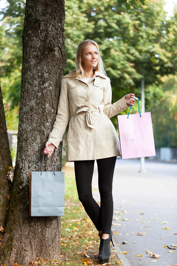 Autumn shopping. Beautiful woman with shopping bags walking on the street of autumn city royalty free stock photos