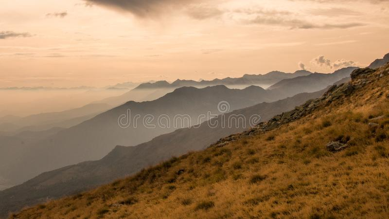 Autumn sky and clouds over the mountains. It`s nearly winter and the snow is about to appear over the mountain peaks, fog down the valley autumn to winter stock photography