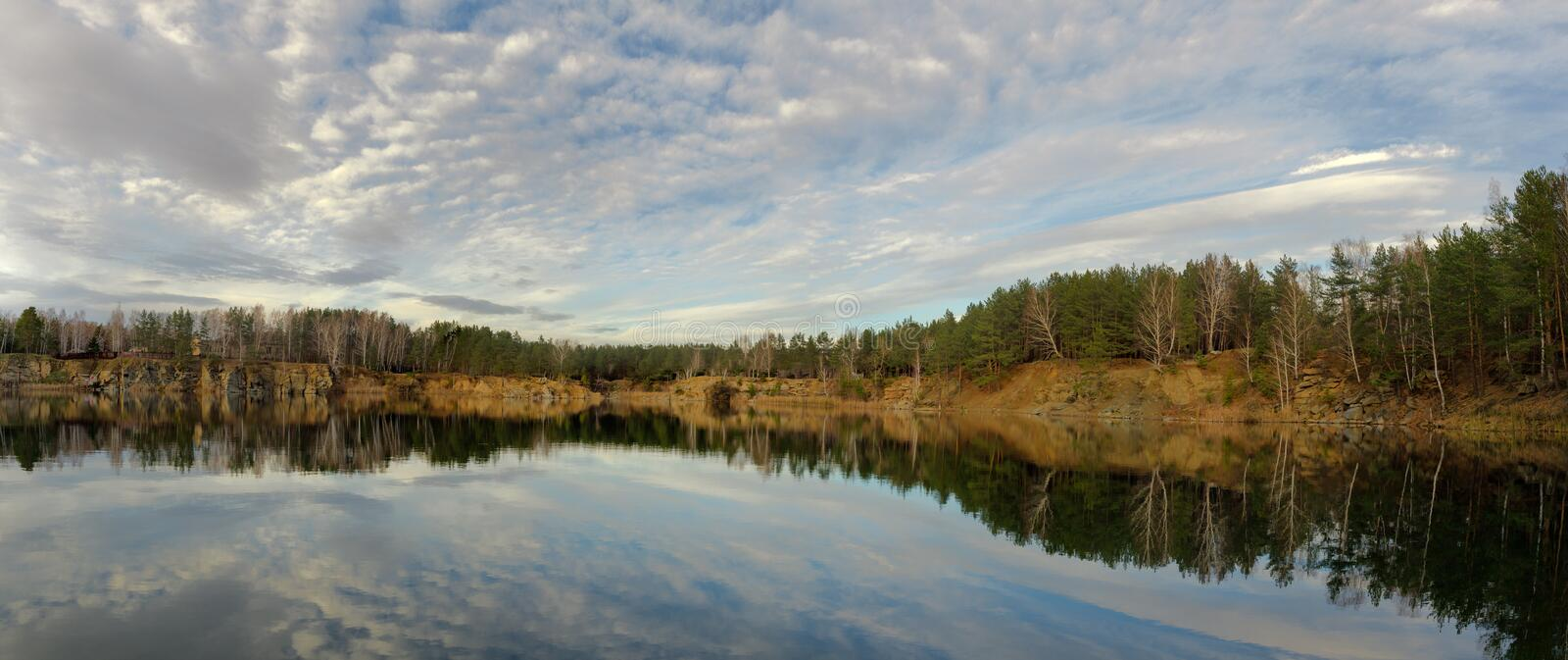 Autumn sky with light clouds over a body of water. Blue Quarry, Chelyabinsk royalty free stock images