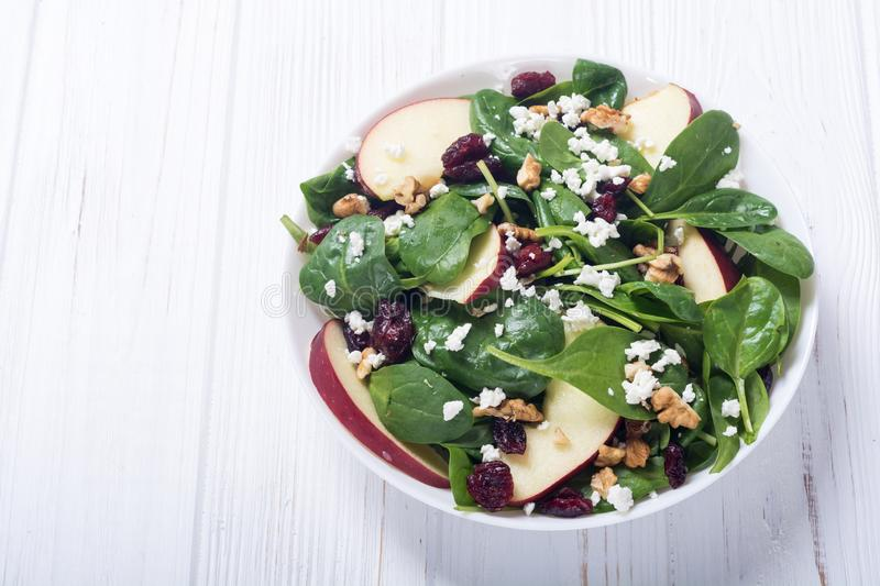 Autumn spinach salad with apple cheese , walnut and dried cranberry . Healthy vegetarian food. Autumn spinach salad with apple , cheese , walnut and dried royalty free stock image