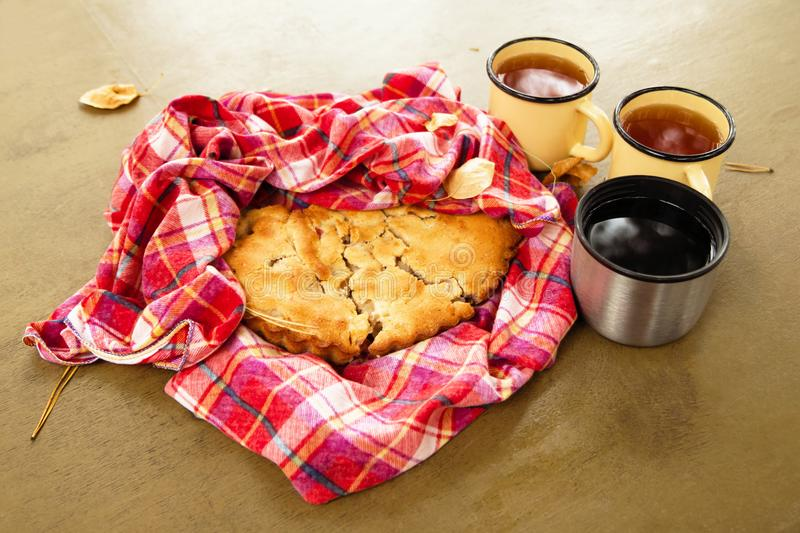 Autumn still life with apple pie on a red checkered towel and three cups of tea on a table. Picnic in a park stock image
