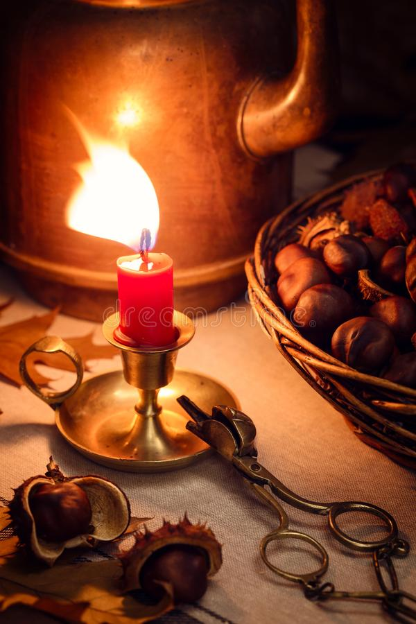 Autumn still life with a candle, chestnuts and an old copper coffeepot royalty free stock photo