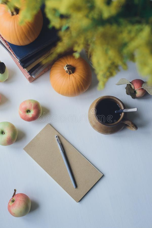 Autumn still life with closed notebook with pencil, books, pumpkins, apple, cup, bouquet royalty free stock image