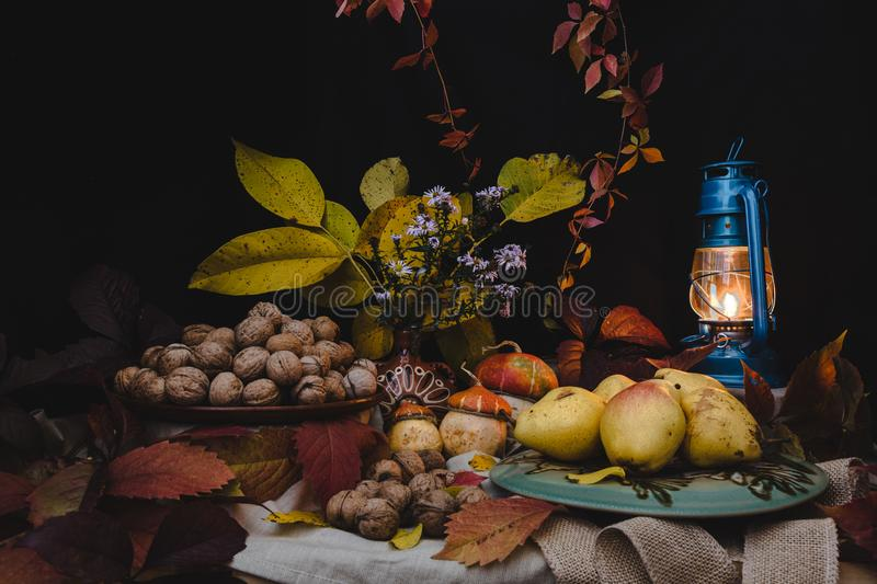 The autumn still life is decorated with a pear, walnut, pumpkin royalty free stock photography