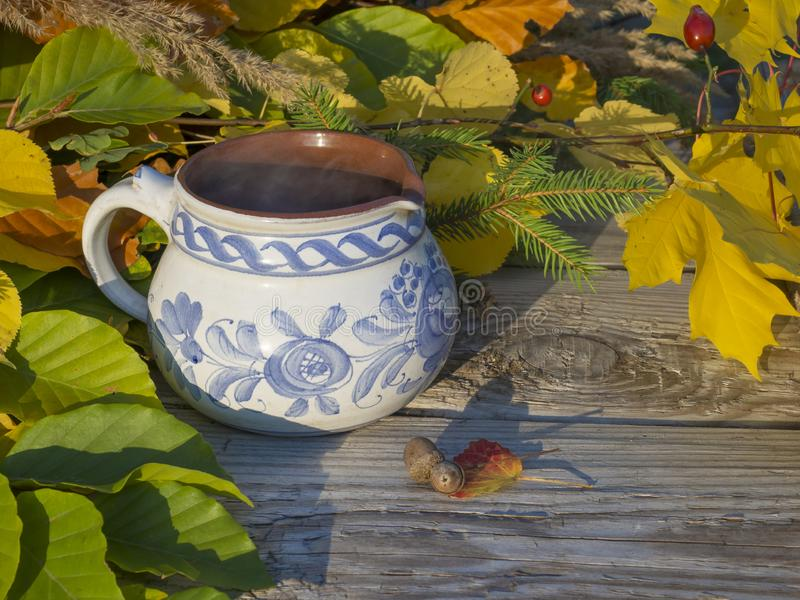 Autumn still life, hot smoking tea in rustic white blue painted ceramic cup with colorful autumn colored leaves, beech and maple t stock photo