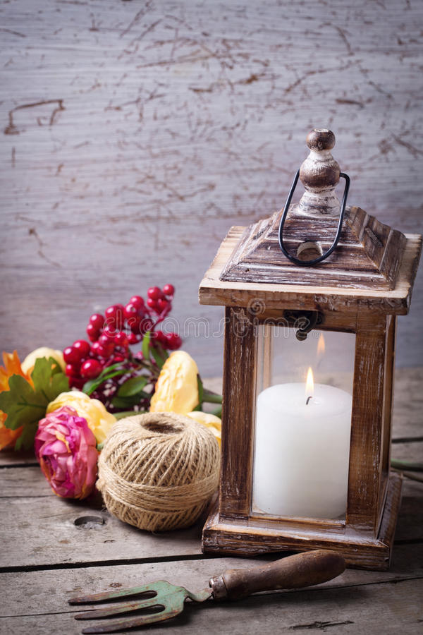 Autumn still life photo with candle in lantern and flowers royalty free stock photo