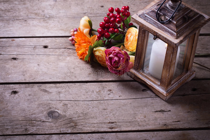 Autumn still life photo with candle in lantern and flowers royalty free stock images
