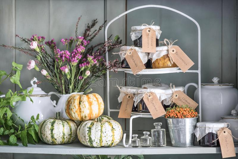 Autumn still life. Pumpkins, mint, dry flowers, heather, cloves, jars with waiting and old dishes stock images