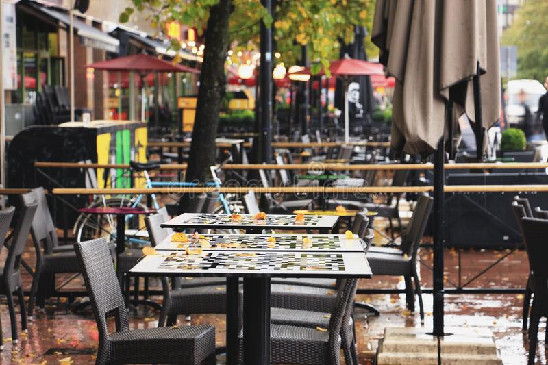 Autumn street cafe with fallen leaves on tables royalty free stock photo