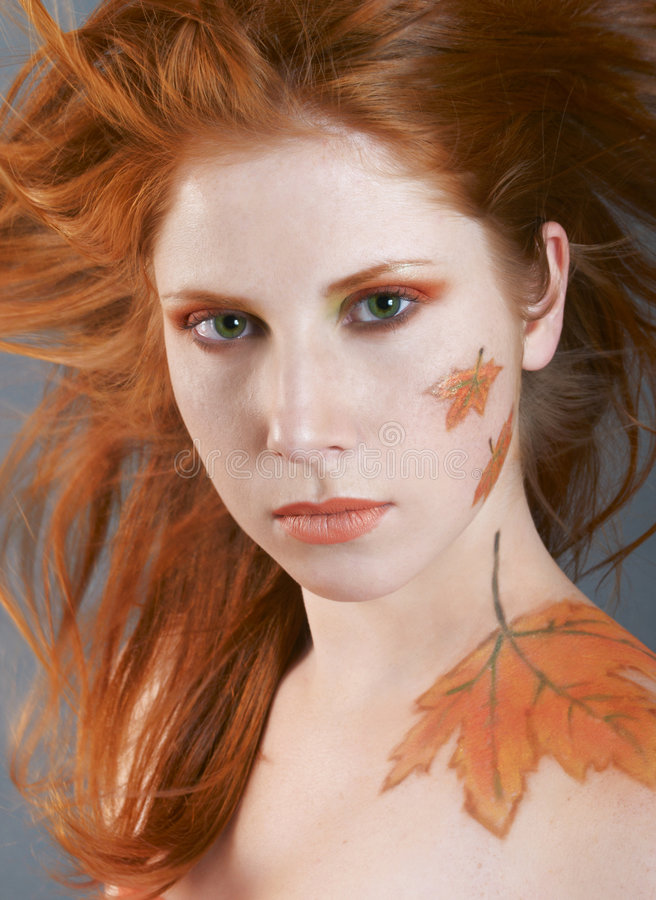 Autumn style face-art. Beautiful with autumn style face-art make-up and red hair stock photography