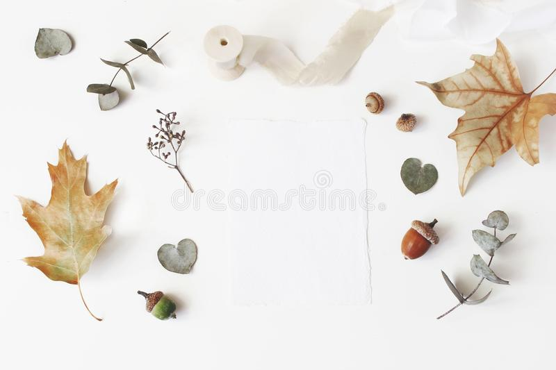Autumn styled stock photo. Feminine wedding desktop stationery mockup scene with blank greeting card, dry eucalyptus. Maple, oak leaves and silk ribbon on stock photo