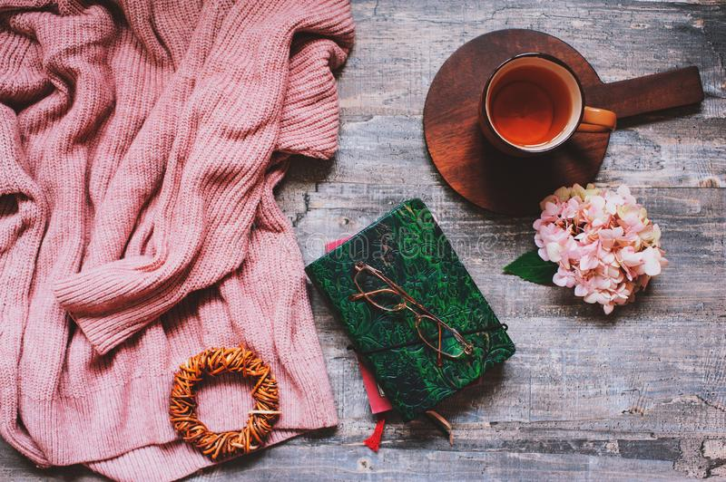 Autumn or summer garden table top view with cozy sweater, coffee, glasses, sketch book, dried hydrangea flowers royalty free stock images