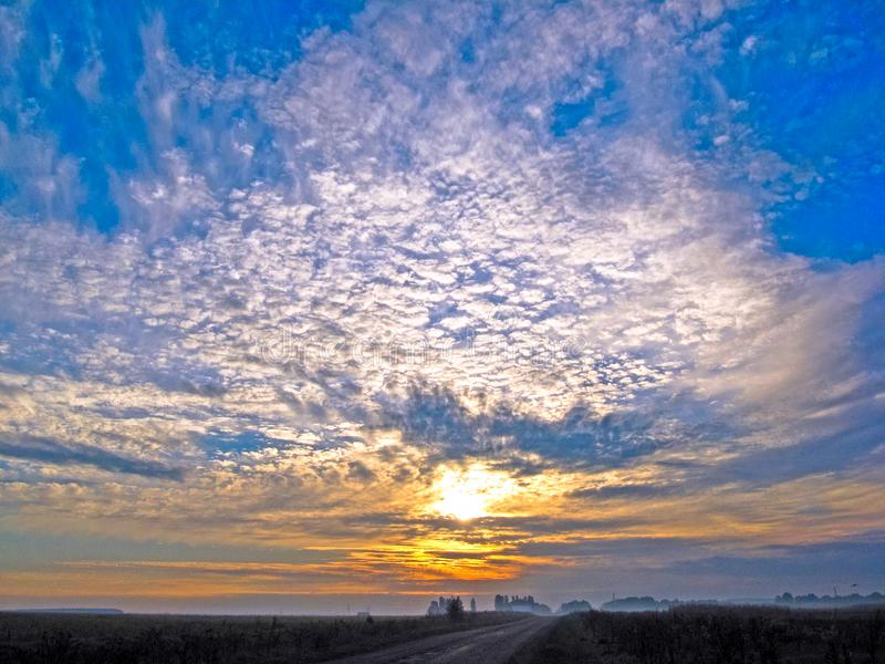 Autumn sunrise with fog. The sun`s rays of the morning sun break through the clouds against the blue sky stock photography