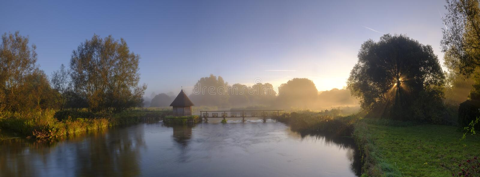 Autumn sunrise with mist on the Eel House traps on the River Test near Longstock, Hampshire, UK. Longstock, UK - September 2018: Autumn sunrise with mist on the royalty free stock images