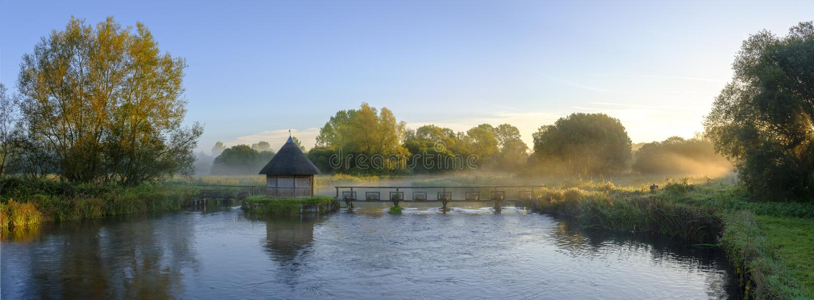 Autumn sunrise with mist on the Eel House traps on the River Test near Longstock, Hampshire, UK royalty free stock photos