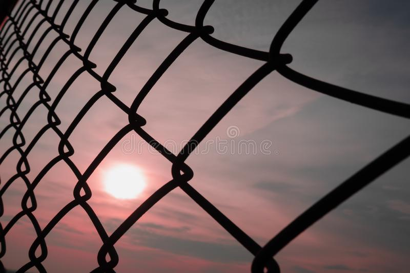 Autumn sunrise shining through the metal chain link fence background texture. Soft focus scenery of autumn sunrise shining through the metal chain link fence stock image