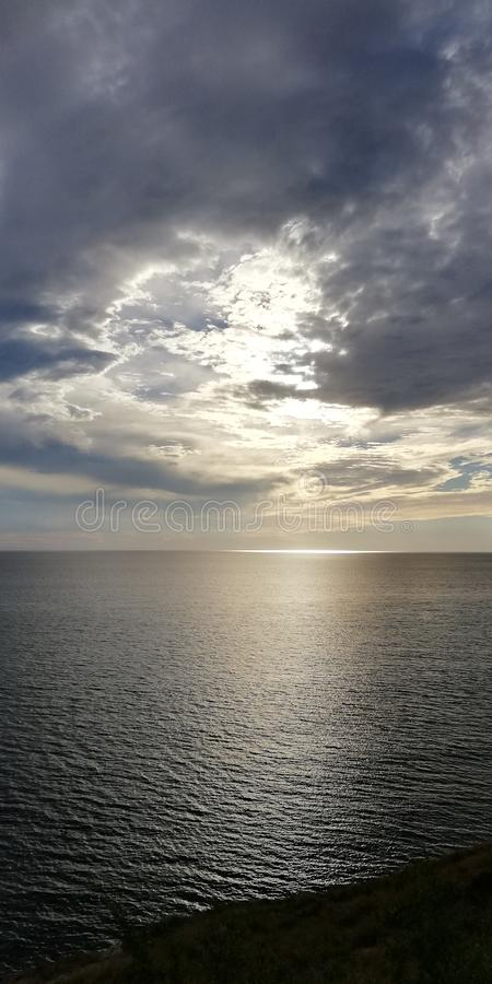 Autumn sunset seascape. Clouds, sea and setting sun. Background. The autumn severe dark sea is illuminated by the setting sun, peeking through dense blue-gray royalty free stock images