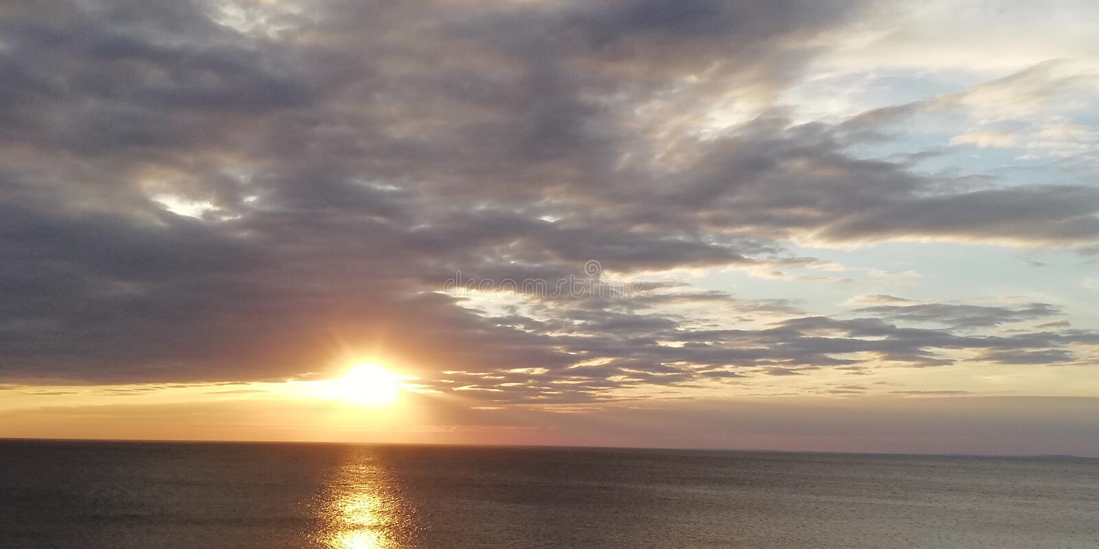 Autumn sunset seascape. Clouds, sea and setting sun. Bright beautiful background. The autumn severe dark sea is illuminated by the setting sun, peeking through royalty free stock image