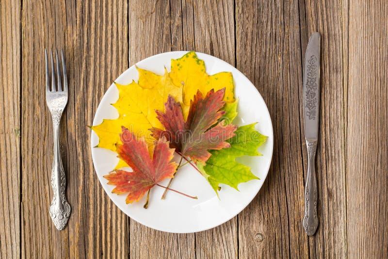 Autumn Table Setting Danksagungsgroßer Teller mit Gabel, Messer und Blättern auf rustikalem Holztischhintergrund lizenzfreies stockbild