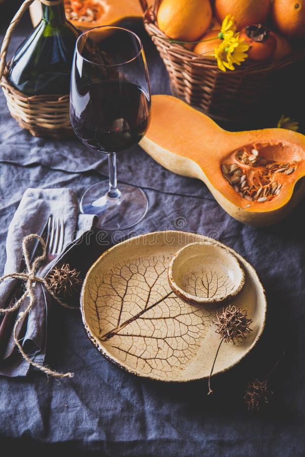 Autumn table setting with pumpkins, basket and red wine. Fall home decoration for festive dinner royalty free stock images