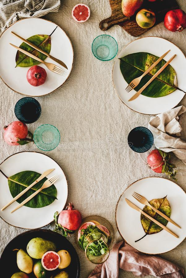 Autumn table setting with seasonal fruits and fallen leaves royalty free stock images