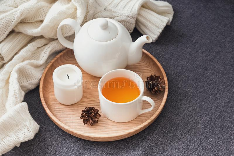 Autumn tea at home. Teapot, cup and candle on the wooden tray standing on the sofa stock image