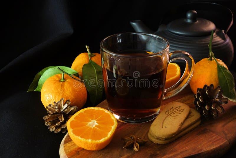 Autumn Tea Une tasse de thé noir, une cuillère, feuilles d'automne, mandarines Ginger Cookies Fond noir images libres de droits