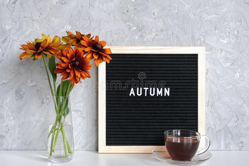 Autumn text on black letter board, bouquet of orange flowers in vase and cup of tea on table against grey stone wall. Template for royalty free stock photography